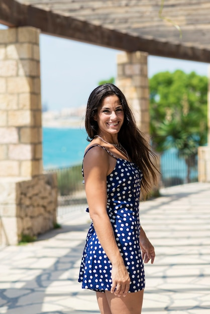 Linda mulher hispânica no vestido azul em pé ao ar livre enquanto olha para a câmera Foto Premium