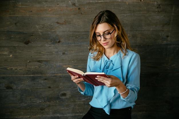 Linda mulher inteligente bonita em óculos lendo livro interessante, parece pensativo Foto gratuita