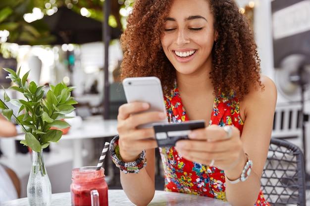 Linda mulher jovem de pele escura com expressão alegre, segura telefone inteligente e cartão de crédito, bancos on-line ou faz compras enquanto se senta no interior do café. Foto gratuita