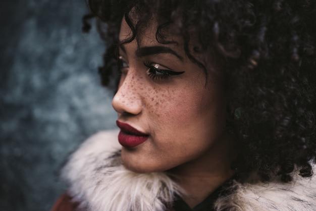 Linda mulher latina com cabelos cacheados, retrato situado na cidade Foto Premium