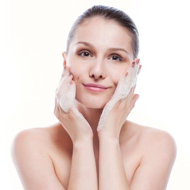 Linda mulher lavando o rosto dela - isolado no branco Foto Premium