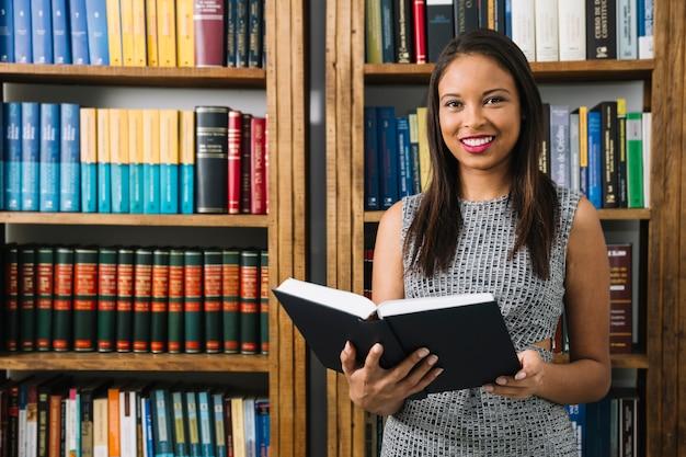 Linda mulher lendo livro na biblioteca Foto gratuita