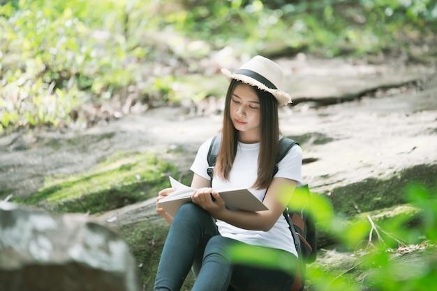 Linda mulher lendo livro na natureza Foto gratuita