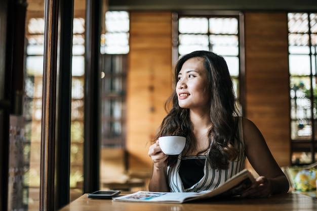 Linda mulher lendo revista no café Foto gratuita