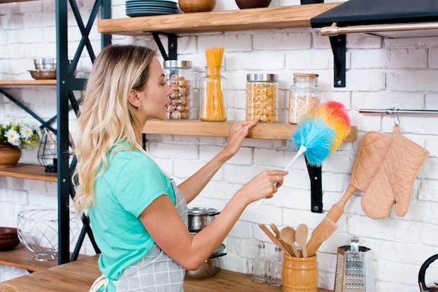Linda mulher, limpeza de prateleira de cozinha com espanador macio Foto gratuita