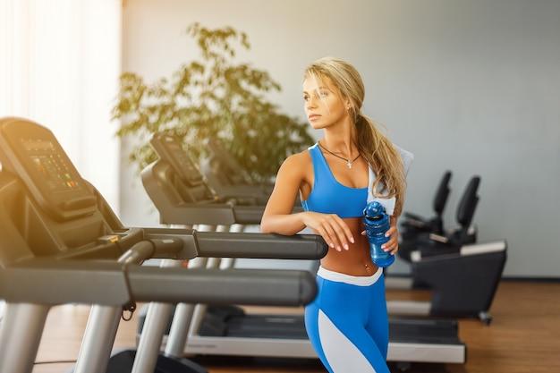 Linda mulher loira atlética é água potável em uma esteira na academia Foto Premium
