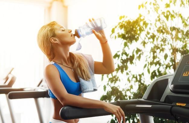 Linda mulher loira atlética é água potável em uma esteira na academia. Foto Premium
