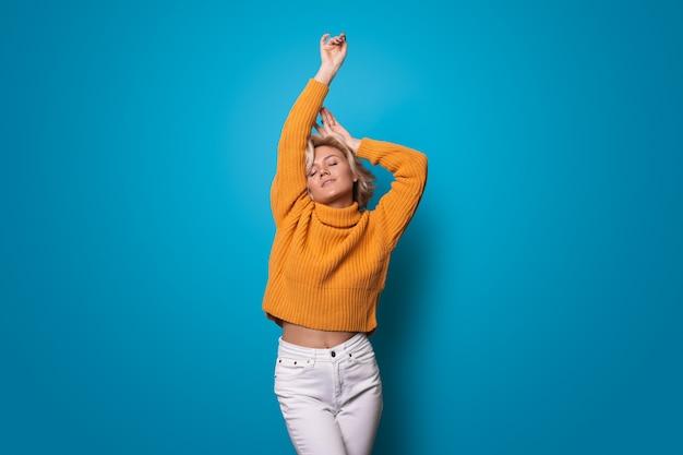 Linda mulher loira caucasiana com suéter amarelo posando com a mão acima na parede azul Foto Premium