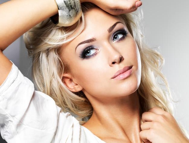 Linda mulher loira com cabelo longo cacheado e estilo de maquiagem. garota posando em estúdio Foto gratuita