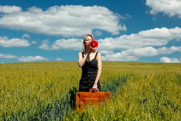 Linda mulher loira com mala e megafone no campo de trigo em dia de sol Foto Premium