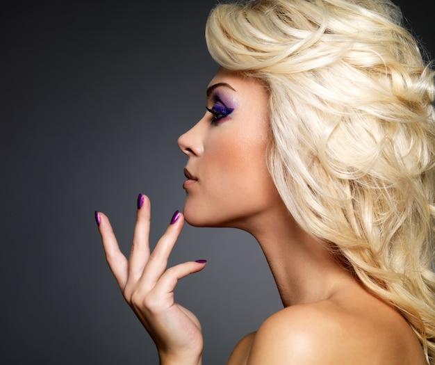 Linda mulher loira com manicure de beleza roxa e maquiagem dos olhos. modelo com penteado encaracolado. Foto gratuita
