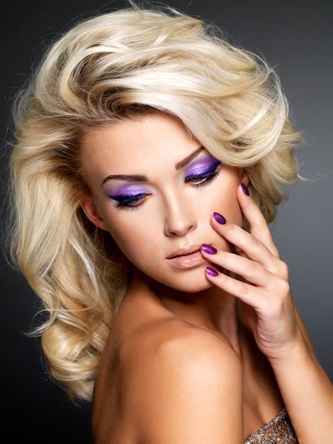 Linda mulher loira com uma bela manicure roxa e maquiagem nos olhos Foto gratuita