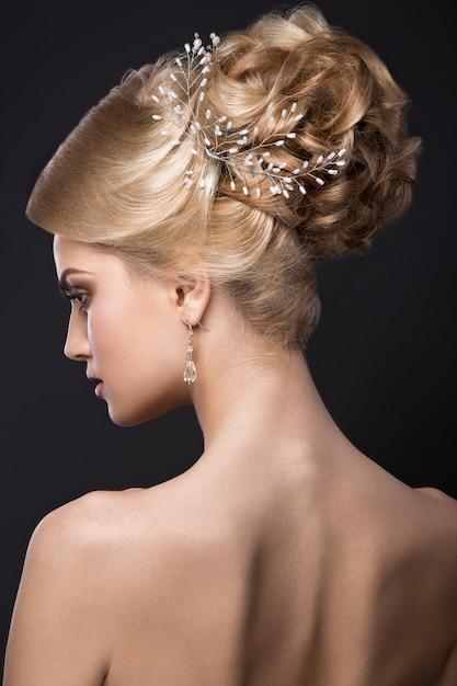 Linda mulher loira com uma pele perfeita, maquiagem de noite, penteado de casamento e acessórios Foto Premium