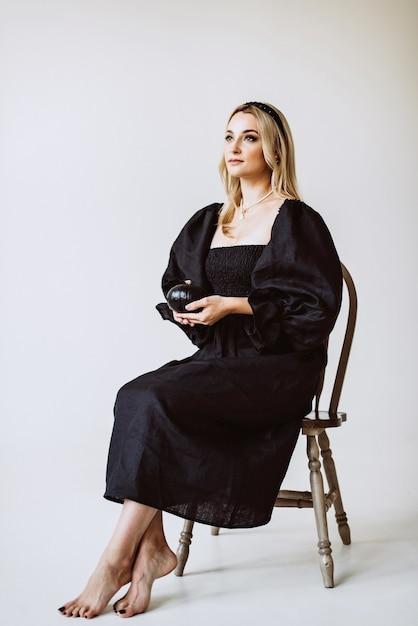Linda mulher loira com vestido de linho preto com uma abóbora nas mãos. moda étnica, tecido natural. foco seletivo suave. Foto Premium
