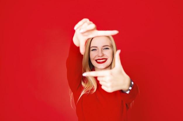 Linda mulher loira mostrando a figura quadrada dos dedos Foto Premium