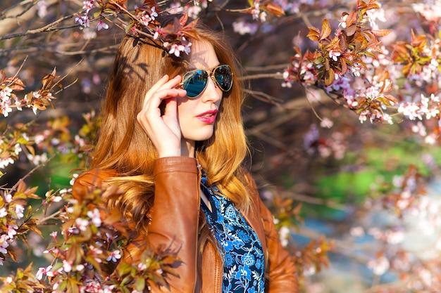 Linda mulher loira no parque em um dia quente de primavera Foto gratuita