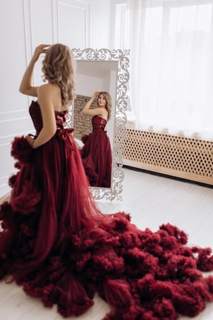 Linda mulher loira no vestido de luxo vermelho burgundi coloca antes de um espelho em um quarto branco Foto gratuita