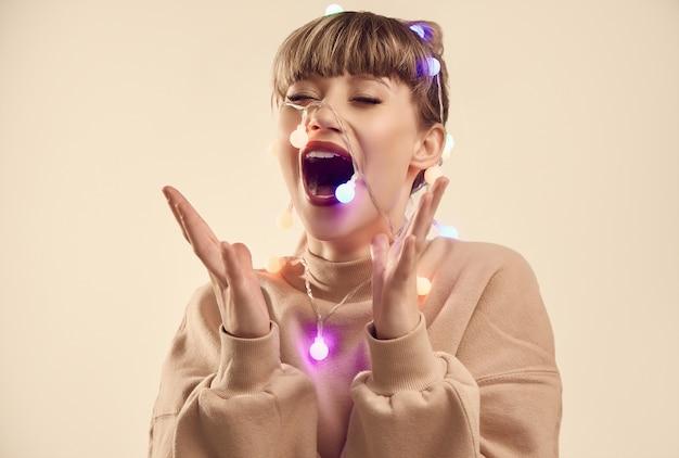 Linda mulher loira positiva com luzes de natal na cabeça Foto Premium