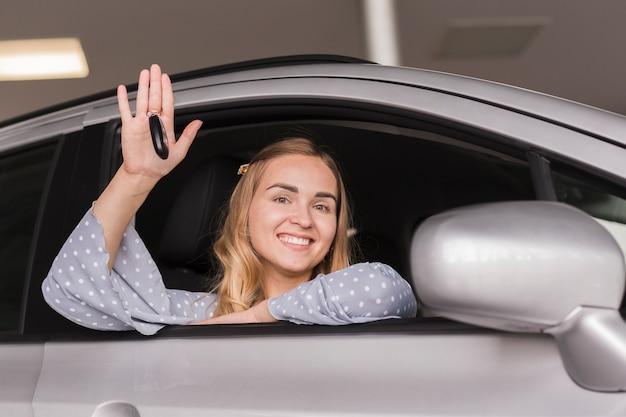 Linda mulher loira saudando de um carro Foto gratuita