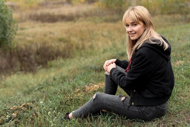 Linda mulher loira sentada na natureza Foto gratuita