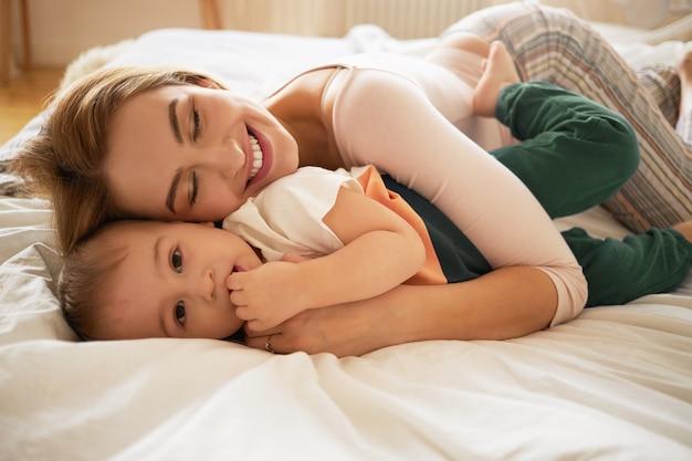 Linda mulher loira sorrindo amplamente deitada na cama desfeita e abraçando o filho da criança acordada. aconchegante e doce foto de linda mãe e filho se relacionando no quarto. família, amor, cuidado e carinho Foto gratuita