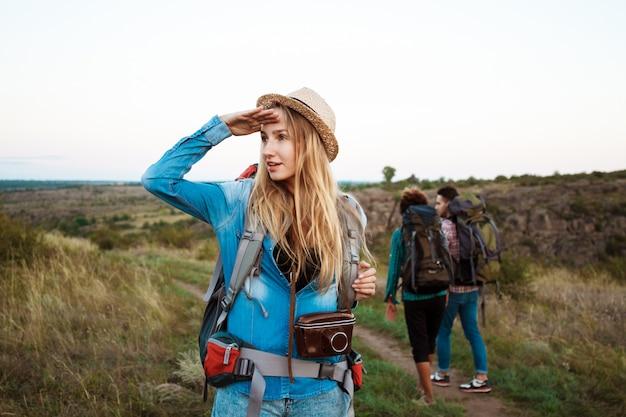 Linda mulher loira sorrindo, olhando para a distância, amigos turistas fundo Foto gratuita