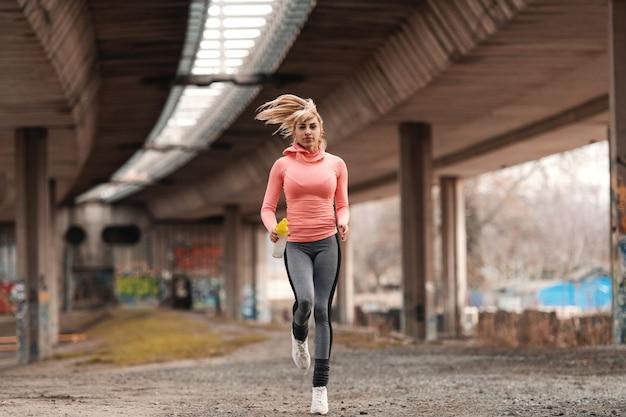 Linda mulher loira vestida de sportswear correndo debaixo da ponte e segurando a garrafa com água. Foto Premium
