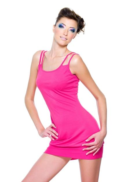 Linda mulher magra posando em um vestido rosa isolado no branco Foto gratuita