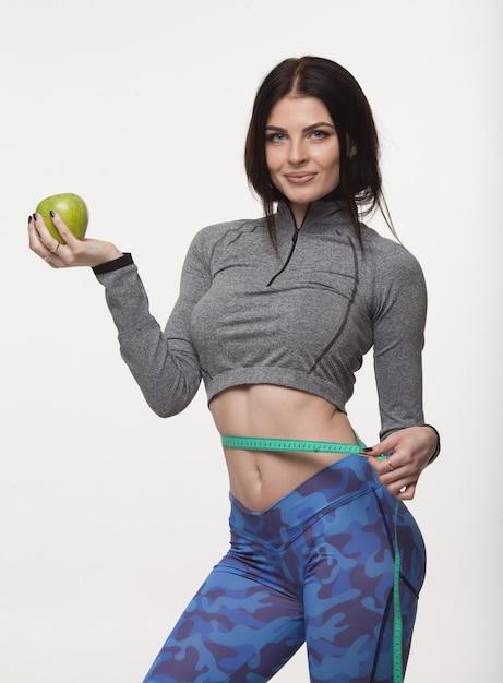 Linda mulher magro, segurando a maçã verde e com várias fitas de medição de cor na cintura Foto Premium