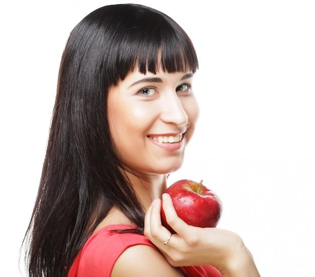 Linda mulher morena com maçã vermelha nas mãos Foto Premium