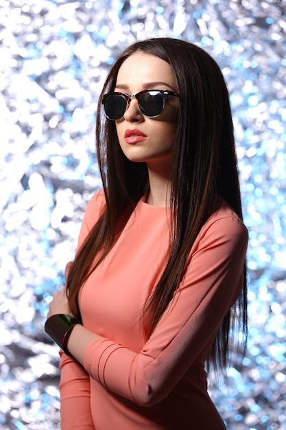 Linda mulher morena com óculos escuros e cabelos longos posando Foto Premium
