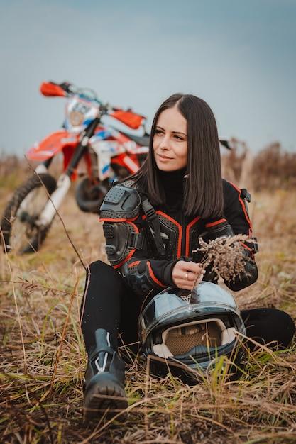 Linda mulher morena com roupa de moto. piloto de motocross feminino ao lado de sua motocicleta rússia moscou 20 de outubro de 2019 Foto Premium