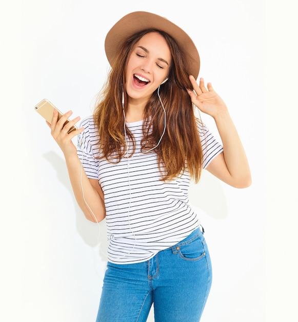 Linda mulher morena sorridente em roupas de verão casual hipster sem maquiagem no chapéu marrom, ouvindo música no telefone com fones de ouvido isolados no branco Foto gratuita