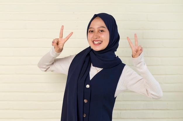 Linda mulher muçulmana asiática em hijab mostrando paz ou gesto de vitória com a mão Foto Premium