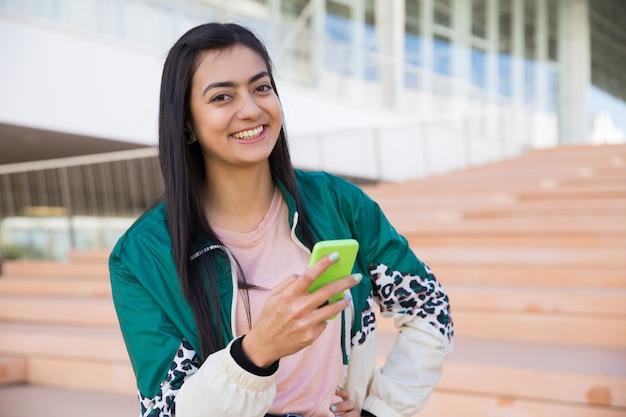 Linda mulher na escada segurando o telefone na mão, sorrindo Foto gratuita