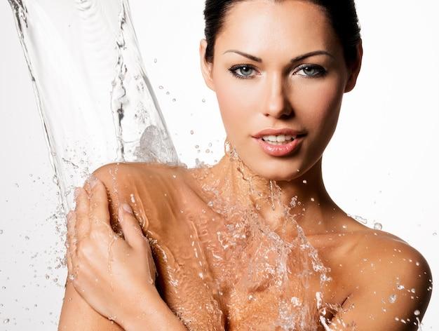 Linda mulher nua com corpo molhado e respingos de água Foto gratuita
