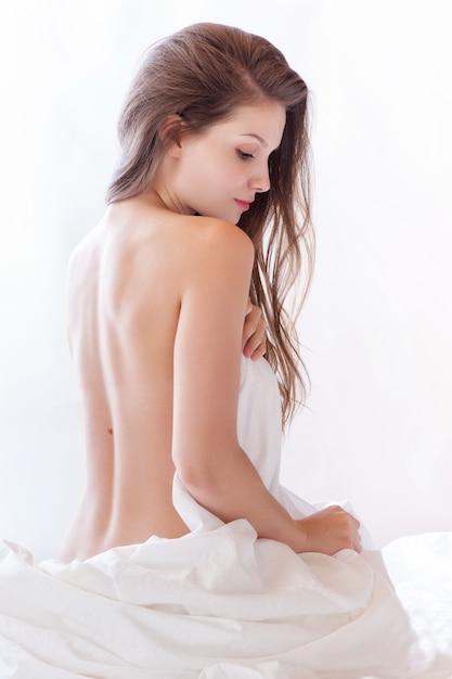 Linda mulher nua deitada na cama e cobrindo-se com lençol branco Foto Premium
