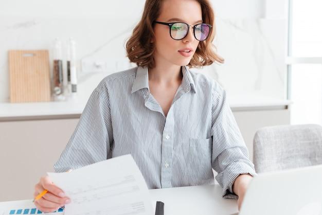 Linda mulher pensativa em óculos e camisa listrada, trabalhando com documentos em casa Foto gratuita