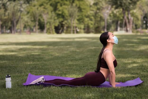 Linda mulher praticando ioga ao ar livre Foto gratuita