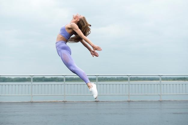 Linda mulher pulando tiro no escuro Foto gratuita