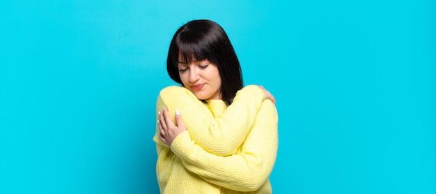 Linda mulher se sentindo apaixonada, sorrindo, se abraçando e se abraçando, permanecendo solteira, sendo egoísta e egocêntrica Foto Premium