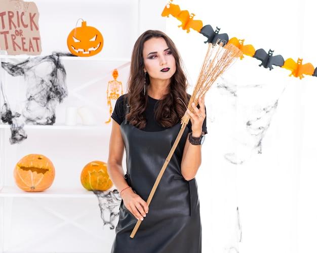 Linda mulher segurando a vassoura de halloween Foto gratuita