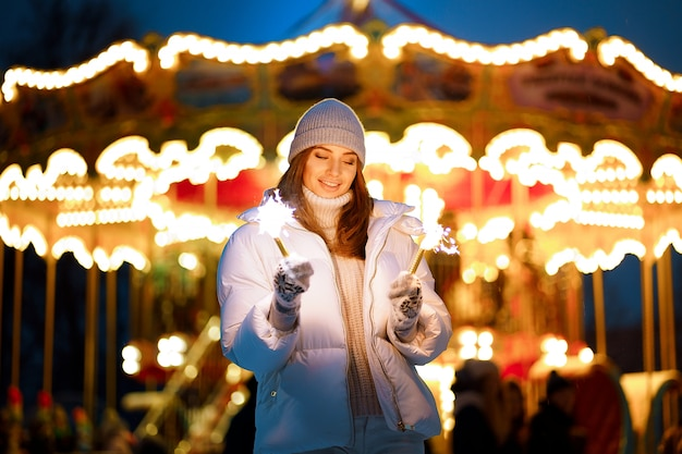 Linda mulher segurando brilhos e divirta-se ao ar livre Foto Premium