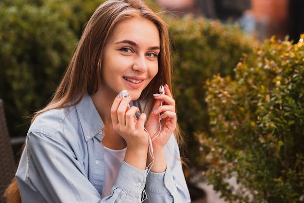 Linda mulher segurando fones de ouvido Foto gratuita