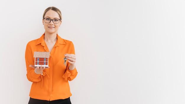 Linda mulher segurando modelo de casa e chave na frente da parede branca Foto gratuita
