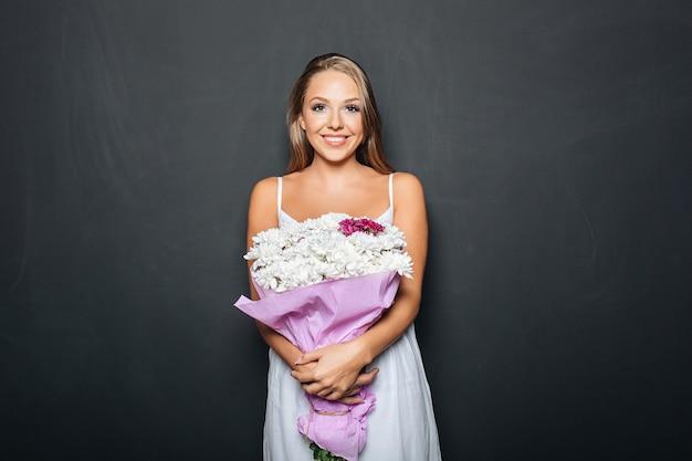 Linda mulher segurando ramo de flores Foto gratuita