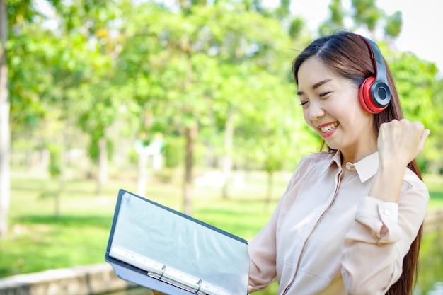 Linda mulher segurando um arquivo e usando fones de ouvido, ela está feliz em trabalhar. Foto Premium