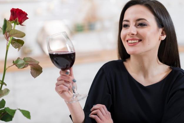 Linda mulher segurando um copo de vinho tinto Foto gratuita