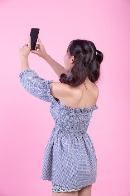 Linda mulher segurando um smartphone em um fundo rosa. Foto gratuita