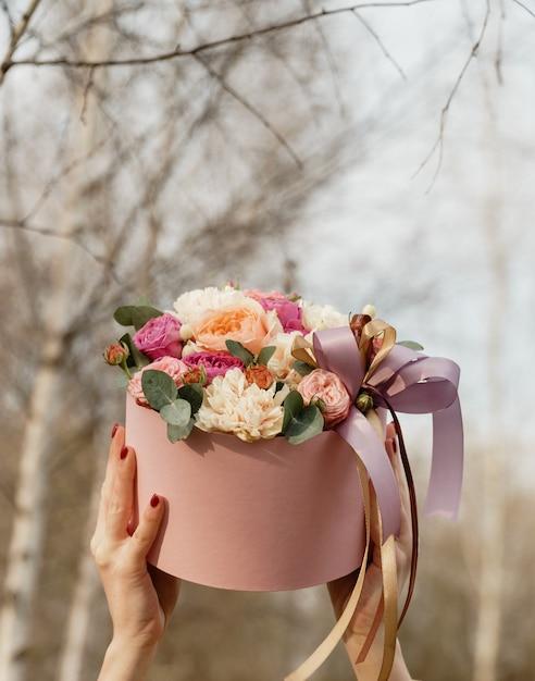Linda mulher segurando uma caixa rosa com flores. presente para o dia da mulher. Foto Premium